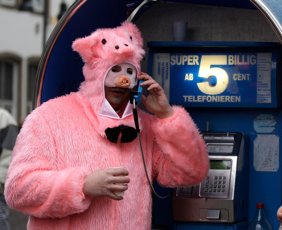 ". A carnival  reveller dressed as a pig uses a phone during the start of the street-carnival with its tradition of fools entering the town halls and women cutting off men\'s ties with scissors on carnival\'s so called ""Old Women\'s Day\"" in Cologne, Germany, Thursday, Feb. 7, 2013. The \""Old Women\'s  Day\""  is traditionally the beginning of  street carnival, the foolish street spectacles in the carnival centers of Duesseldorf, Mainz and Cologne. Advertising reads: Super Cheep, calls up from 5 euro cents (6.9 US cents). (AP Photo/Frank Augstein)"