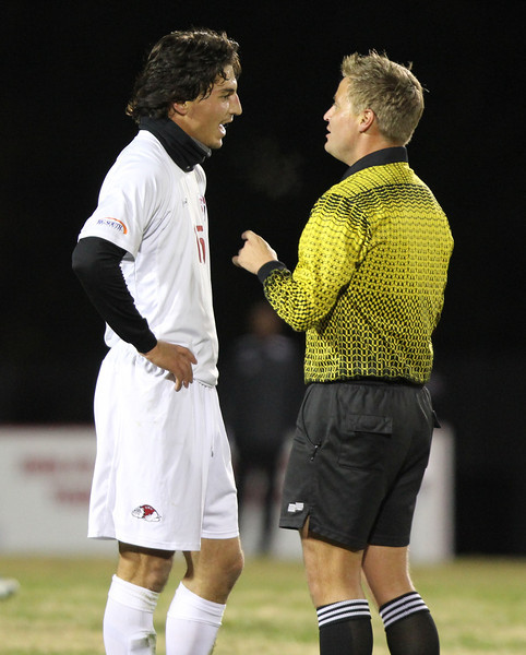 Number 15, Jovan Ivanovich, discusses a call with the referee.