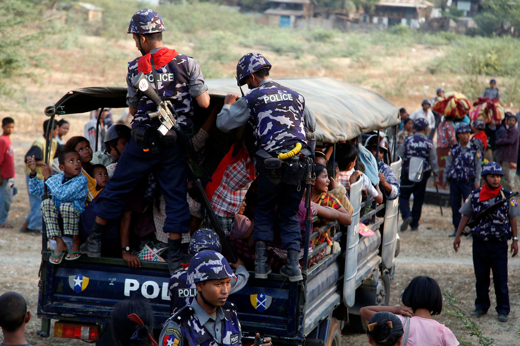 . Myanmar polices help Muslim refugees to move a rescue camp in Meikhtila  about 550 kilometers (340 miles) north of Yangon, Myanmar, Friday, March 22, 2013. (AP Photo/Khin Maung Win)