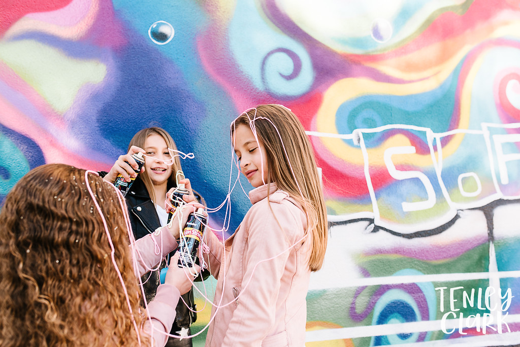 Colorful and fun sisters photography session with Tenley Clark Photography. Downtown San Jose, murals, gymnastics and silly string.
