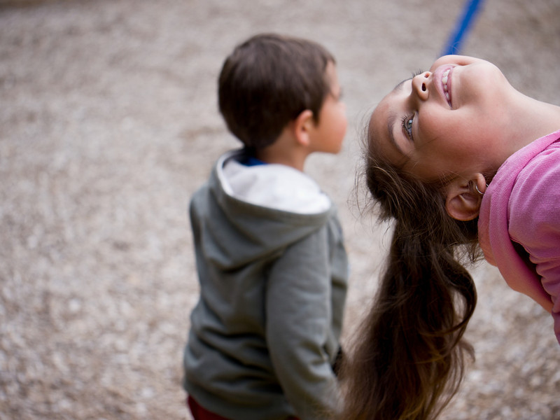 This photo shows happy little girl with her head back on a swing.  In the background is a five year old Aboriginal boy.