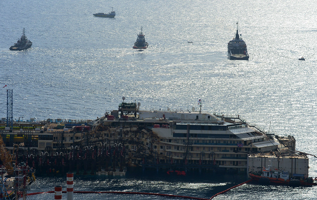 . A general view shows tug boats near the wreck of the Costa Concordia cruise ship during an operation to refloat the liner on July 14, 2014 off the Giglio Island. Over two and a half years after it crashed off the island of Giglio in a nighttime disaster which left 32 people dead, the plan is to raise and tow away the 114,500-tonne vessel in an unprecedented and delicate operation for its final journey to the shipyard where it was built in the port of Genoa.          (VINCENZO PINTO/AFP/Getty Images)