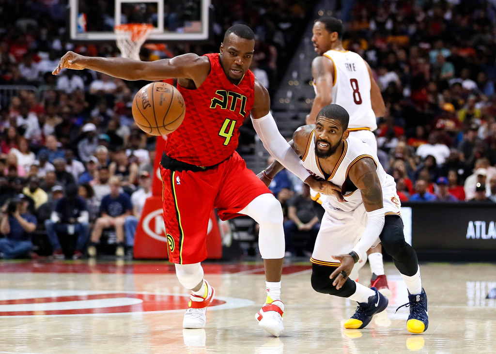 . Atlanta Hawks forward Paul Millsap (4) and Cleveland Cavaliers guard Kyrie Irving (2) fight for the ball in the second half of an NBA basketball game on Sunday, April 9, 2017, in Atlanta. The Hawks won in overtime 126-125. (AP Photo/Todd Kirkland)