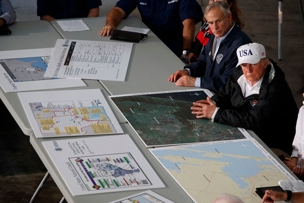 . Texas Gov. Greg Abbot and President Donald Trump listen during a briefing on Harvey relief efforts, Tuesday, Aug. 29, 2017, in Corpus Christi, Texas. (AP Photo/Evan Vucci)