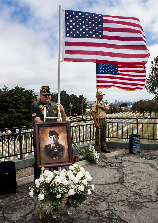 . Army veteran Jeff McFall holds the American flag behind a photo of Sgt. 1st Class Joseph Steinberg who was interred at Golden Gate National Cemetery in San Bruno, Calif., on Aug. 1, 2013. Steinberg who disappeared as a POW during the Korean War, died on April 30, 1951. His remains were recently identified with the use of DNA and returned 62 years after he went missing. Steinberg was interred at Golden Gate National Cemetery alongside his three brothers, all of whom were WWII veterans. (John Green/Bay Area News Group)