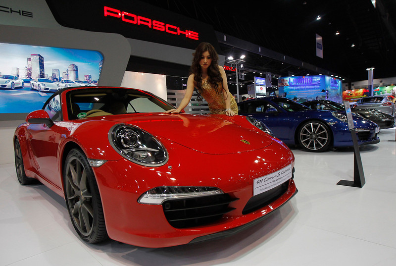 . A model poses beside a Porsche 911 Carrera S Cabriolet during a media presentation of the 34th Bangkok International Motor Show in Bangkok March 26, 2013. The Bangkok International Motor Show will be held from March 27 to April 7. REUTERS/Chaiwat Subprasom