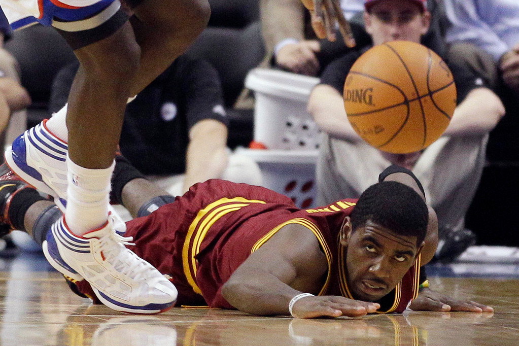 . Cleveland Cavaliers\' Kyrie Irving, right, cannot reach a loose ball against Philadelphia 76ers\' Jrue Holiday in the second half of an NBA basketball game, Tuesday, March 27, 2012, in Philadelphia. Philadelphia won 103-85. (AP Photo/Matt Slocum)