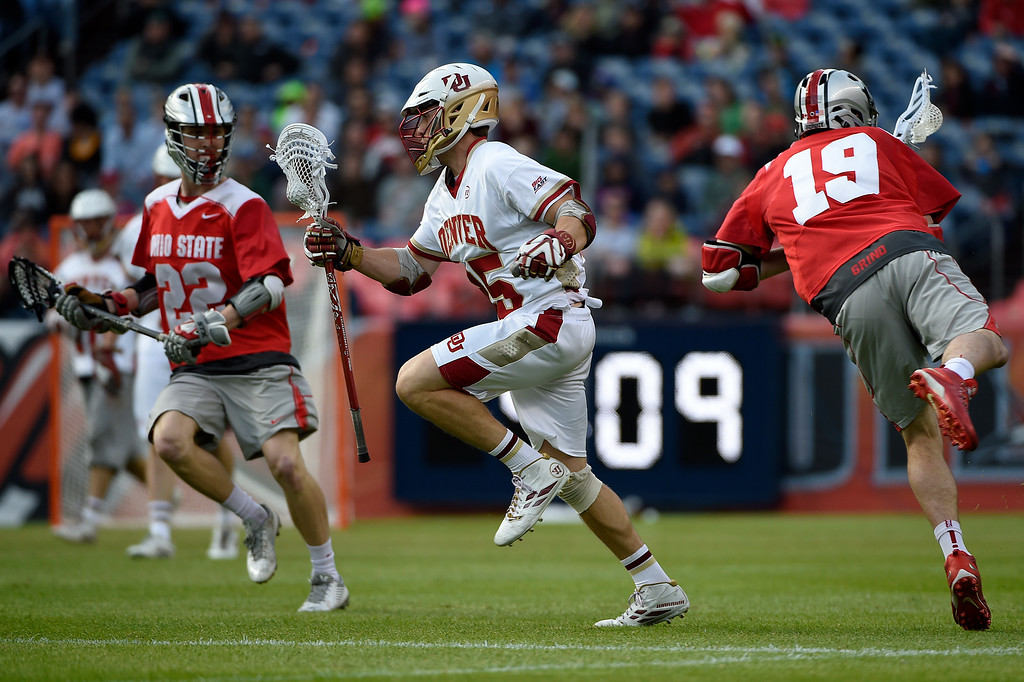 . Garret Holst (25) of the Denver Pioneers cuts up defenders  Colin Chell (22) of the Ohio State Buckeyes and  Jesse King (19) during the first half of their NCAA tournament quarterfinal match. The Denver Pioneers played the Ohio State Buckeyes at Sports Authority field at Mile High on Saturday, May 16, 2015. (Photo by AAron Ontiveroz/The Denver Post)