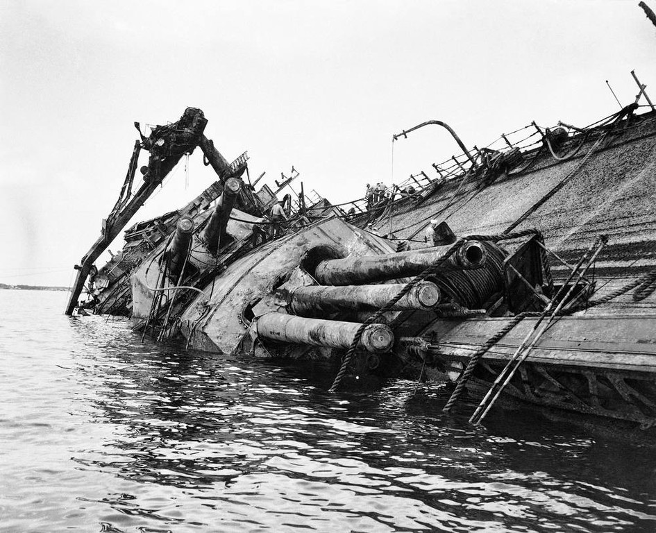 . In this image provided by the U.S. Navy, the barnacled deck of the U.S S. Oklahoma breaks water in Pearl Harbor on May 24, 1943, during salvage operations which returned to service 16 of 19 ships sunk by the Japanese on Dec. 7, 1941. (AP Photo/U.S. Navy)