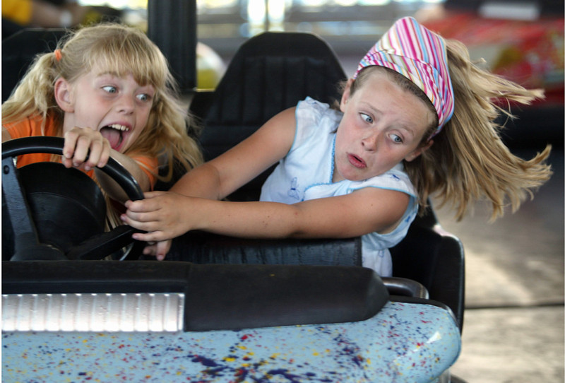 Grace Beattie, 7 (left) and Emily Imbuelten, 7, (right) get knocked around on the Scooter bumper cars at the Silver Dollar Fair Saturday afternoon. - Halley photo 5/28/05