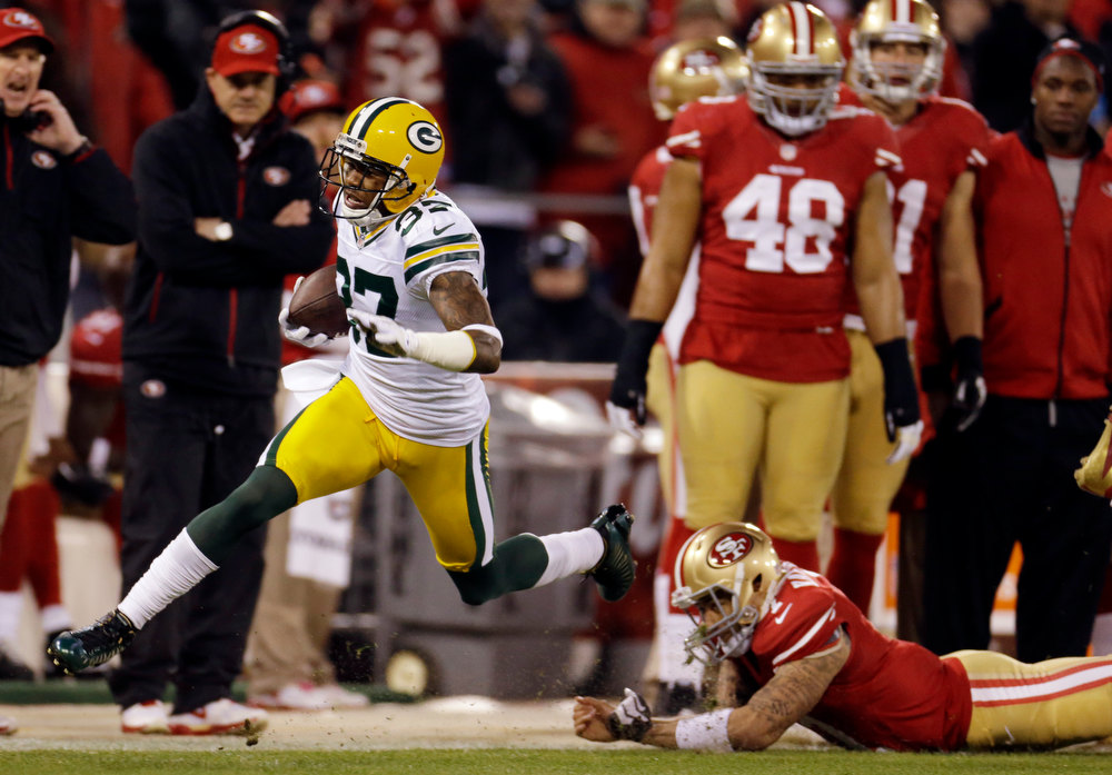 . Green Bay Packers cornerback Sam Shields (37) returns an interception for a touchdown as he dives past San Francisco 49ers quarterback Colin Kaepernick (7) during the first quarter of an NFC divisional playoff NFL football game in San Francisco, Saturday, Jan. 12, 2013. (AP Photo/Ben Margot)