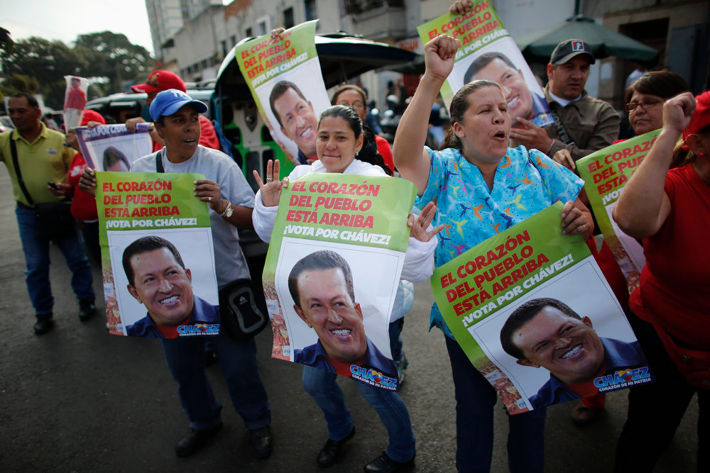 Description of . Supporters of Venezuela's President Hugo Chavez cheer outside the military hospital after his surprise return to Caracas February 18, 2013. Chavez made a surprise return from Cuba on Monday more than two months after surgery for cancer that has jeopardized his 14-year rule of the South American OPEC member. The 58-year-old socialist leader underwent a six-hour operation in Cuba on December 11. He had not been seen or heard in public since then until photos were published of him on Friday. REUTERS/Jorge Silva