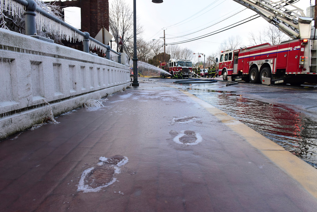. Footprints are formed in the ice at the scene of a 2nd Alarm fire at a vacant mill on McBride Ave. in Paterson, N.J., Wednesday, Dec. 27, 2017.  (Tariq Zehawi/The Record via AP)