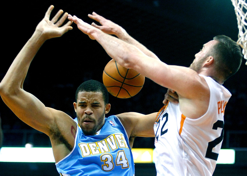 . Denver Nuggets center JaVale McGee (34), left, is fouled by Phoenix Suns center Miles Plumlee (22) in the first quarter during an NBA basketball game on Friday, Nov. 8, 2013, in Phoenix. (AP Photo/Rick Scuteri)