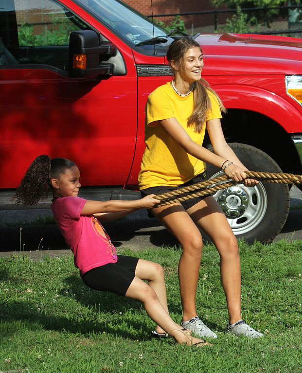 . National Night Out, at North Common, organized by the Lowell Police Department. Lilyana Oquendo, 7, of Lowell teams up with Caroline Rizos, 16, of Lowell, a summer employee of Lowell Parks & Rec, to do tug-of-war. (SUN/Julia Malakie)