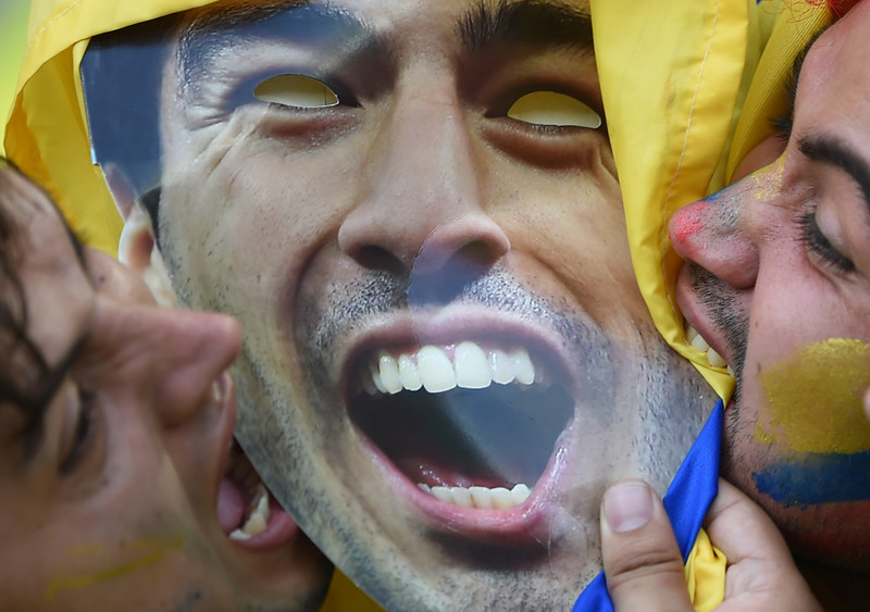 . Uruguay\'s fans bite a cardboard cut out of Uruguayan forward Luis Suarez prior to the Round of 16 football match between Colombia and Uruguay at the Maracana Stadium in Rio de Janeiro during the 2014 FIFA World Cup in Brazil on June 28, 2014. (EITAN ABRAMOVICH/AFP/Getty Images)