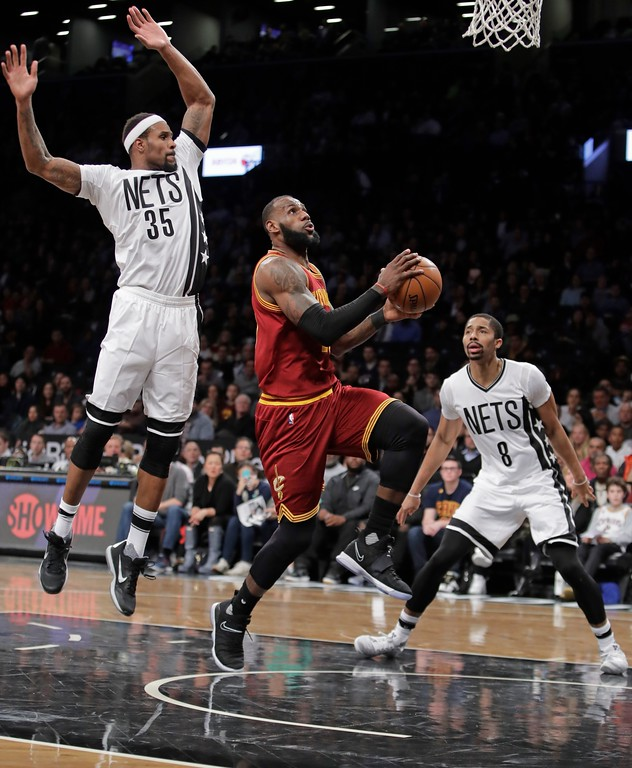 . Cleveland Cavaliers\' LeBron James (23) drives past Brooklyn Nets\' Spencer Dinwiddie (8) and Trevor Booker (35) during the first half of an NBA basketball game Friday, Jan. 6, 2017, in New York. (AP Photo/Frank Franklin II)