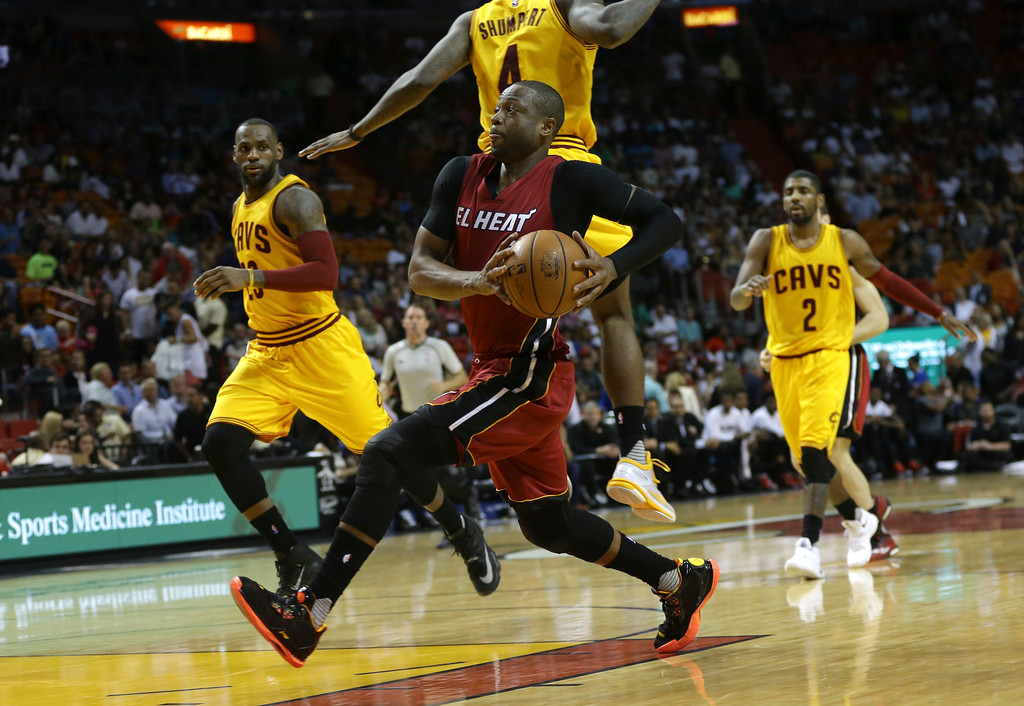 . Miami Heat guard Dwyane Wade, center, drives to the basket as Cleveland Cavaliers forward LeBron James, left, looks on during the second half of an NBA basketball game, Saturday, March 19, 2016, in Miami. (AP Photo/Lynne Sladky)