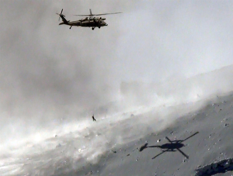. This aerial picture taken on September 28, 2014 shows a helicopter of Japan\'s Self Defense Force lifting a survivor from volcanic ash covered top of Mount Ontake at Nagano prefecture, one day after Japan\'s volcano Ontake erupted in central Japan, which straddling Nagano and Gifu prefecture. Rescuers rushed to help dozens of hikers stranded on an erupting volcano in central Japan with six people believed to be buried under ash and dozens injured.  AFP PHOTO / JIJI PRESS