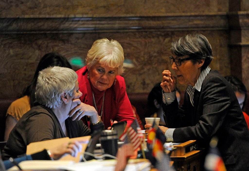 . DENVER, CO. - MARCH 8: Senators Mary Hodge, left, Lois Tochtrop, and Lucia Guzman, right, meet on the Senate floor. Debate begins on the Senate floor at the state capitol on various gun bills before the state legislature. (Photo By Kathryn Scott Osler/The Denver Post)