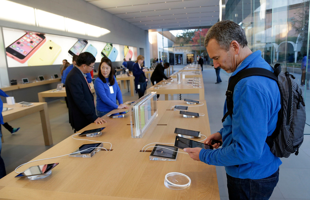 . Customers look at the new iPad Air on Friday, Nov. 1, 2013, in Stanford, Calif. Apple\'s iPad Air, a thinner, lighter and faster-running version of its previous large tablet computers, goes on sale Friday with a starting price of $499. The company also unveiled an updated version of its iPad Mini recently. It goes on sale sometime in November. (AP Photo/Marcio Jose Sanchez)