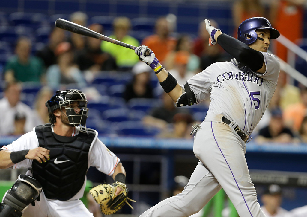 . Colorado Rockies\' Carlos Gonzalez (5) hits a double to score Michael Cuddyer as Miami Marlins catcher Jarrod Saltalamacchia, left, looks on in the eighth inning of a baseball game, Tuesday, April 1, 2014, in Miami. The Marlins defeated the Rockies 4-3. (AP Photo/Lynne Sladky)