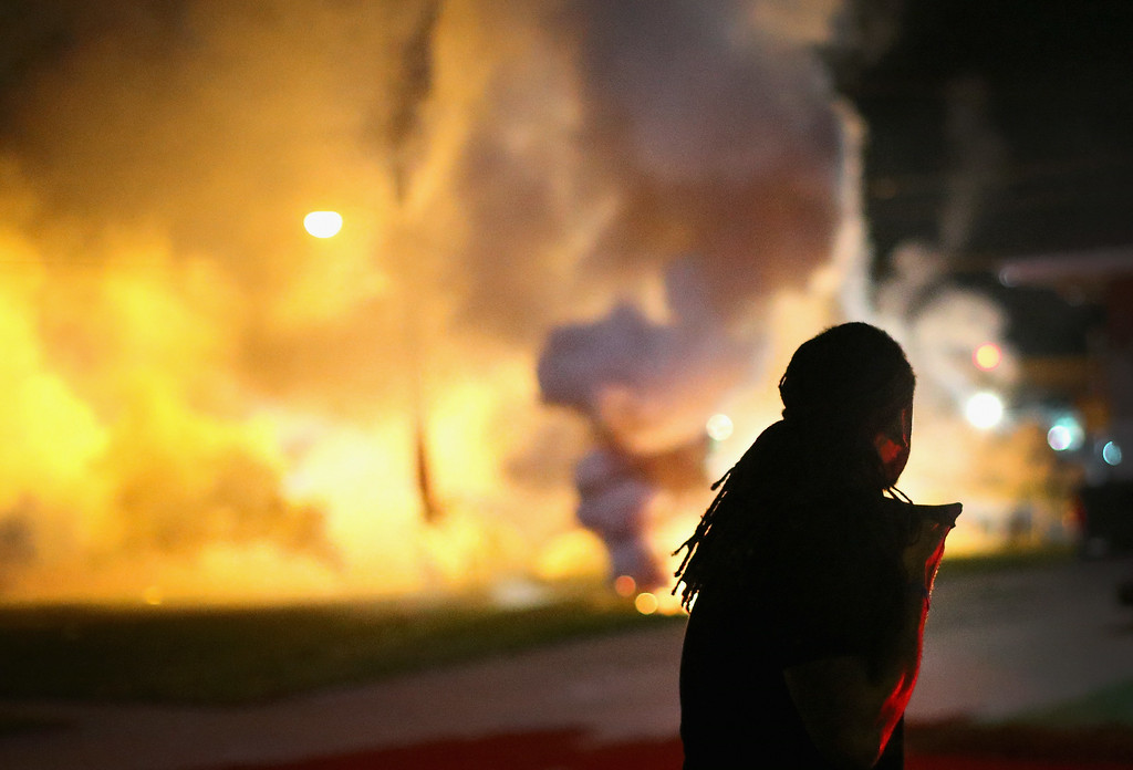 . A demonstrator, protesting the shooting death of teenager Michael Brown, scrambles for cover as police fire tear gas on August 13, 2014 in Ferguson, Missouri. Brown was shot and killed by a Ferguson police officer on Saturday. Ferguson, a St. Louis suburb, is experiencing its fourth day of violent protests since the killing.  (Photo by Scott Olson/Getty Images)