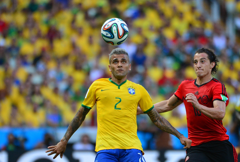 . Brazil\'s defender Dani Alves (L) and Mexico\'s defender Andres Guardado vie for the ball during a Group A football match between Brazil and Mexico in the Castelao Stadium in Fortaleza during the 2014 FIFA World Cup on June 17, 2014. (YURI CORTEZ/AFP/Getty Images)