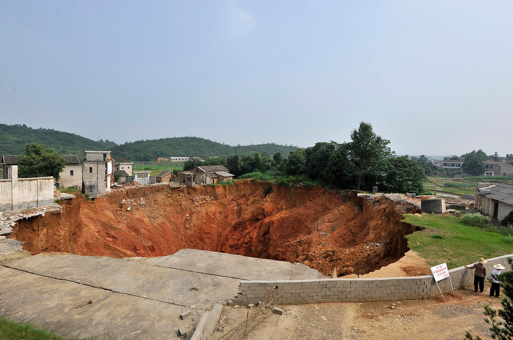 . Local residents look at a sinkhole near Qingquan primary school in Dachegnqiao town of Ningxiang, Hunan province June 15, 2010. The hole, 150 meters (492 feet) wide and 50 meters (164 feet) deep, has been growing since it first appeared in January and has destroyed 20 houses so far. No causalities has been reported and the reason for the appearance of the hole remains unclear, local media reported.  REUTERS/Stringer
