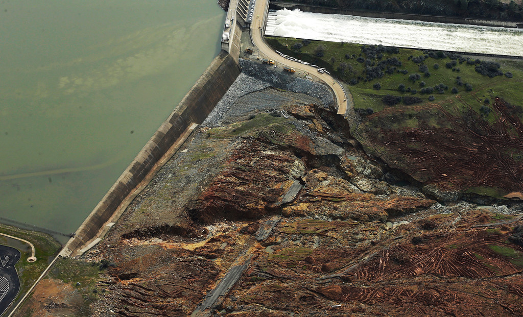 . Erosion caused when overflow water cascaded down the emergency spillway is seen, bottom, as water continues to flow down the main spillway, top, of the Oroville Dam, Monday, Feb. 13, 2017, in Oroville, Calif. The water level dropped Monday at the nation\'s tallest dam, easing slightly the fears of a catastrophic spillway collapse that prompted authorities to order people to leave their homes downstream. (AP Photo/Rich Pedroncelli)