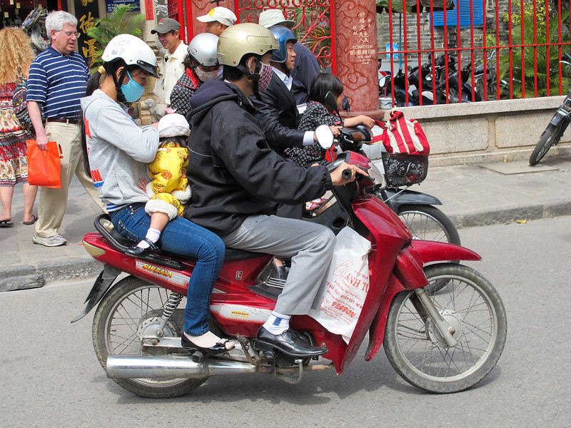 Family of four and family of three on 100 cc [maybe] motorcycle in Hoi An.