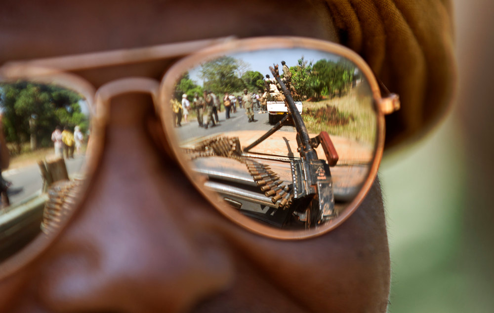 ". A Chadian soldier wearing reflective sunglasses observes the convoy ahead of him, as Chadian soldiers who are fighting in support of Central African Republic president Francois Bozize, ride on the road leading to Damara, about 70km (44 miles) north of the capital Bangui, Central African Republic Wednesday, Jan. 2, 2013. More than 30 truckloads of troops from Chad line the two-lane highway just outside of Damara, supporting government forces who want to block a new rebel coalition from reaching the capital, and Gen. Jean Felix Akaga, who heads a 10-nation regional force, says the town is a ""red line that the rebels cannot cross\"" or his forces will attack. (AP Photo/Ben Curtis)"