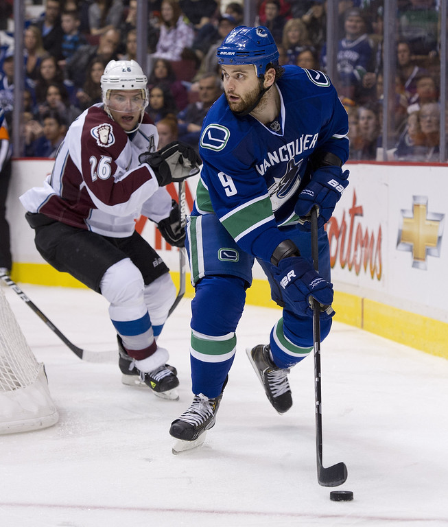 . VANCOUVER, CANADA - JANUARY 30: Zack Kassian #9 of the Vancouver Canucks controls the puck behind the net while being pursued by Paul Stastny #26 of the Colorado Avalanche during the second period in NHL action on January 30, 2013 at Rogers Arena in Vancouver, British Columbia, Canada.  (Photo by Rich Lam/Getty Images)