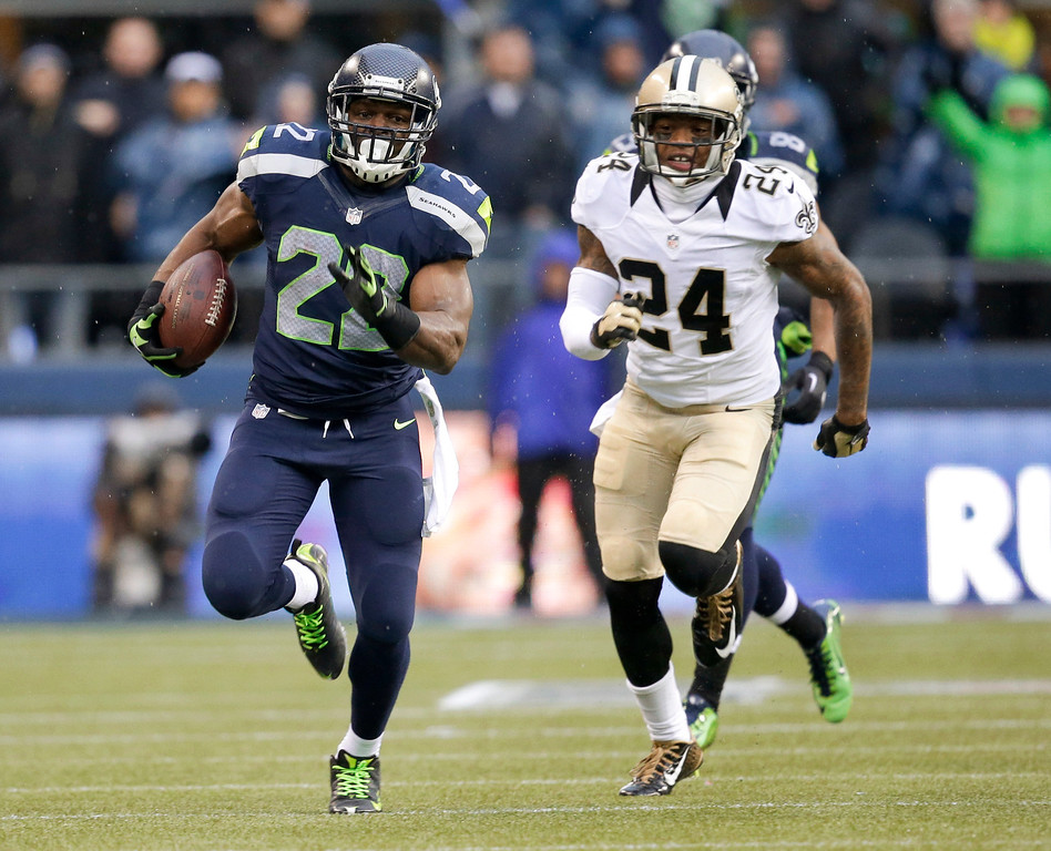 . Seattle Seahawks running back Robert Turbin, left, runs in front of New Orleans Saints cornerback Corey White during the first half of an NFC divisional playoff NFL football game in Seattle, Saturday, Jan. 11, 2014. (AP Photo/Elaine Thompson)
