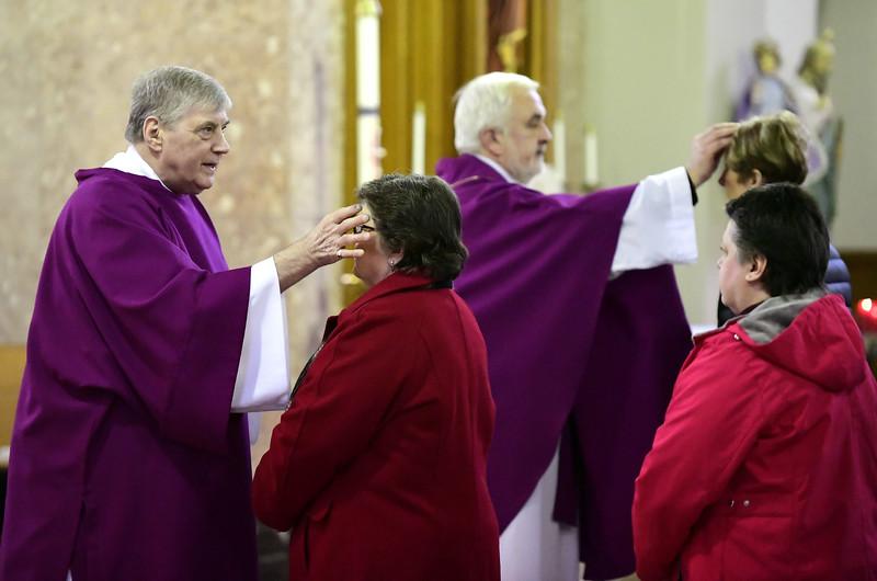 3/6/2019 Mike Orazzi | Staff St Stanislaus Roman Catholic Church Deacon Richard J. Wisniewski and Rev. Tomasz Sztuber apply ashes during Ash Wednesday Mass in Bristol.
