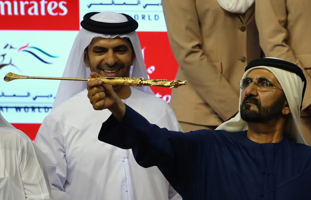 . Sheikh Mohammad Bin Rashid al-Maktoum, ruler of Dubai, spins the golden whip as he celebrates after his horse African Story won the Dubai World Cup, the world\'s richest horse race, at the Meydan race track in the Gulf Emirate on March 29, 2014. A cosmopolitan gathering of horses from seven different countries contested the US$10 million Emirates Dubai World Cup. (MARWAN NAAMANI/AFP/Getty Images)