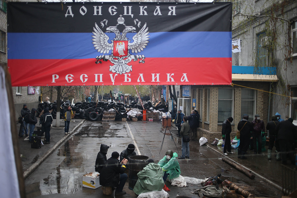 """. Pro-Russian activists gather at a seized police station with a banner reading \""""Donetsk Republic\"""" in the eastern Ukrainian town of Slovyansk on Sunday, April 13, 2014. Ukrainian special forces exchanged gunfire with a pro-Russia militia in the eastern city Sunday, according to the interior minister, who said one Ukrainian security officer was killed and five others wounded. It was the first reported gunbattle in east Ukraine, where armed pro-Russia men have seized a number of law enforcement buildings in recent days. .(AP Photo/Andrew Chernavsky)"""