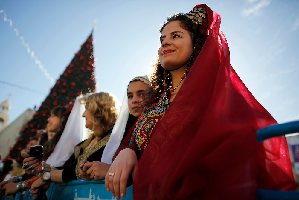 . A Palestinian women dressed in traditional costume watches a Christmas parade outside the Church of Nativity in the West Bank town of Bethlehem on December 24, 2012.  REUTERS/Darren Whiteside