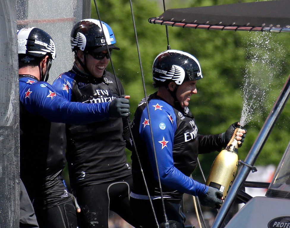 . Ray Davies of the Emirates Team New Zealand crew, right, sprays champagne over the boat and teammates as they celebrate during the America�s Cup World Series sailing event in New York, Sunday, May 8, 2016. Emirates Team New Zealand won the event. (AP Photo/Seth Wenig)