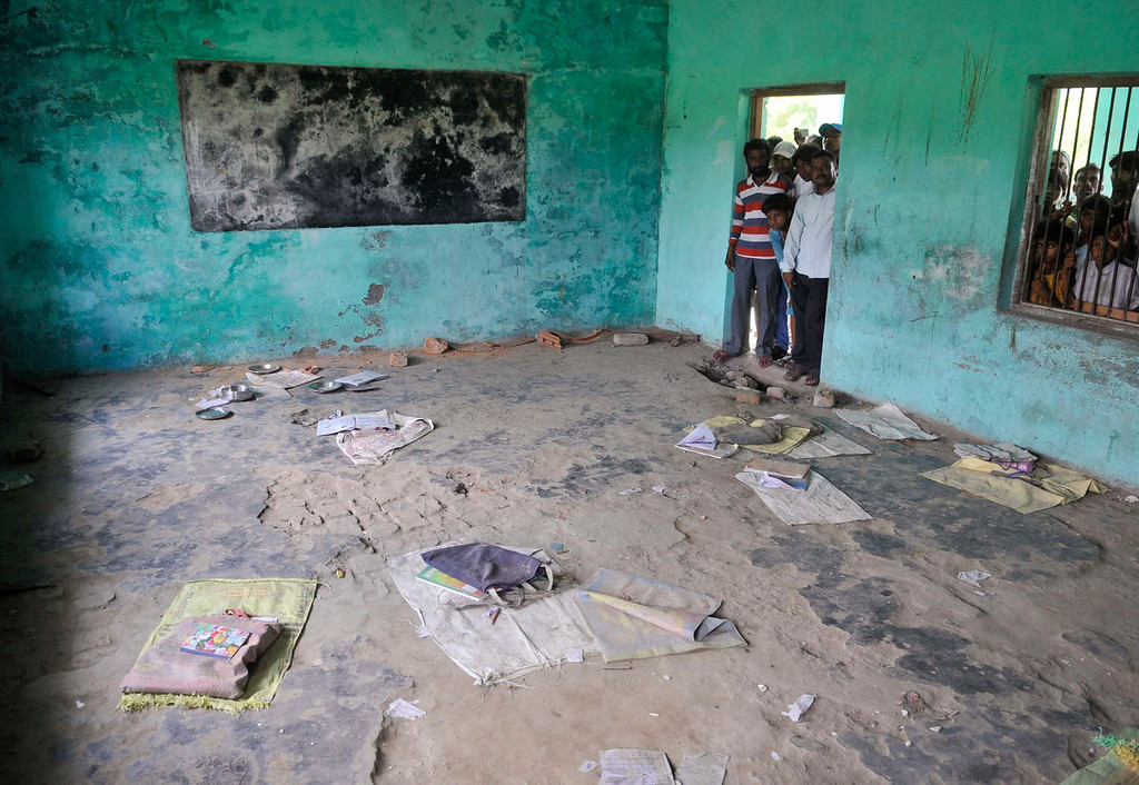 . People look at a classroom where contaminated meals were served to children at a school at Chapra in the eastern Indian state of Bihar July 17, 2013. At least 25 Indian children died and dozens needed hospital treatment after apparently being poisoned by a school meal on Tuesday, sparking violent protests and angry allegations of blame. The school, at Mashrakh village in the district of Chapra, provided free meals under the Mid-Day Meal Scheme, the world\'s largest school feeding program involving 120 million children. Medical teams treating the children said they suspected the food had been contaminated with insecticide.  REUTERS/Stringer