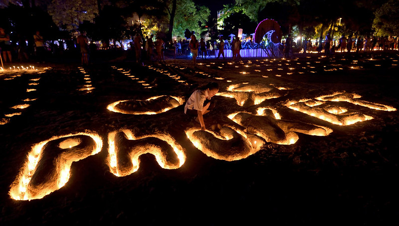 . A Thai student places candles on a sand sculpture during commemorations on the the tenth anniversary of the 2004 tsunami at Patong beach in Phuket province on December 26, 2014. In the morning of December 26, 2004 a 9.3-magnitude earthquake off Indonesia\'s western coast generated a series of massive waves that killed more than 220,000 people across 14 countries as far apart as Indonesia, Sri Lanka and Somalia.  PORNCHAI KITTIWONGSAKUL/AFP/Getty Images