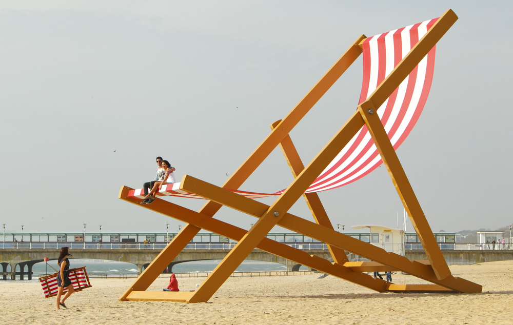 Description of . A couple sit it what is expected to be confirmed as the world's largest deckchair on Bournemouth beach, southern England Thursday March 22, 2012. The giant chair was built by sculptor Stuart Murdoch, weighs almost six tonnes and measures almost 28 feet, 8.5 metres, tall. (AP Photo/PA, Chris Ison)