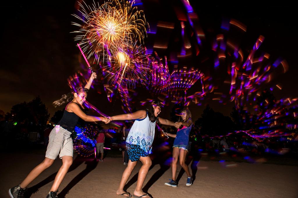 . Cousins, from left, Lenise De La Torre, 8, of Buena Park, Isabella Ochoa, 9, of Anaheim, and Riley Vega, 9, of Buena Park, play with glow sticks during La Mirada\'s annual fireworks show Thursday night, July 3, 2014 at La Mirada Regional Park. (Photo by Sarah Reingewirtz/Pasadena Star-News)