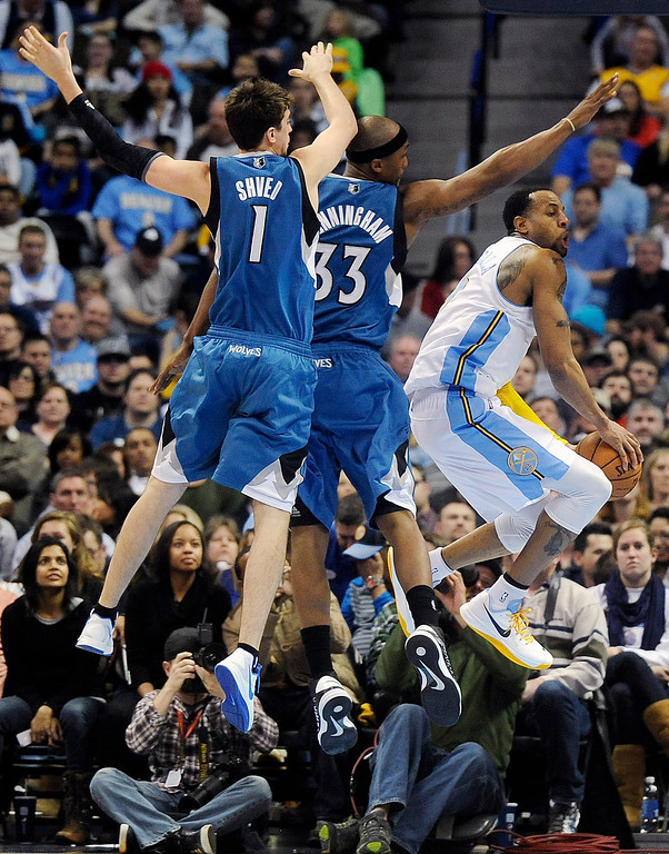 . Denver Nuggets Andre Iguodala, right, looks for an open teammate while being defended by Minnesota Timberwolves guard Alexey Shved, left, of Russia, and forward Dante Cunningham, center, in the second half of an NBA basketball game on Saturday, March 9, 2013, in Denver.  (AP Photo/Chris Schneider)