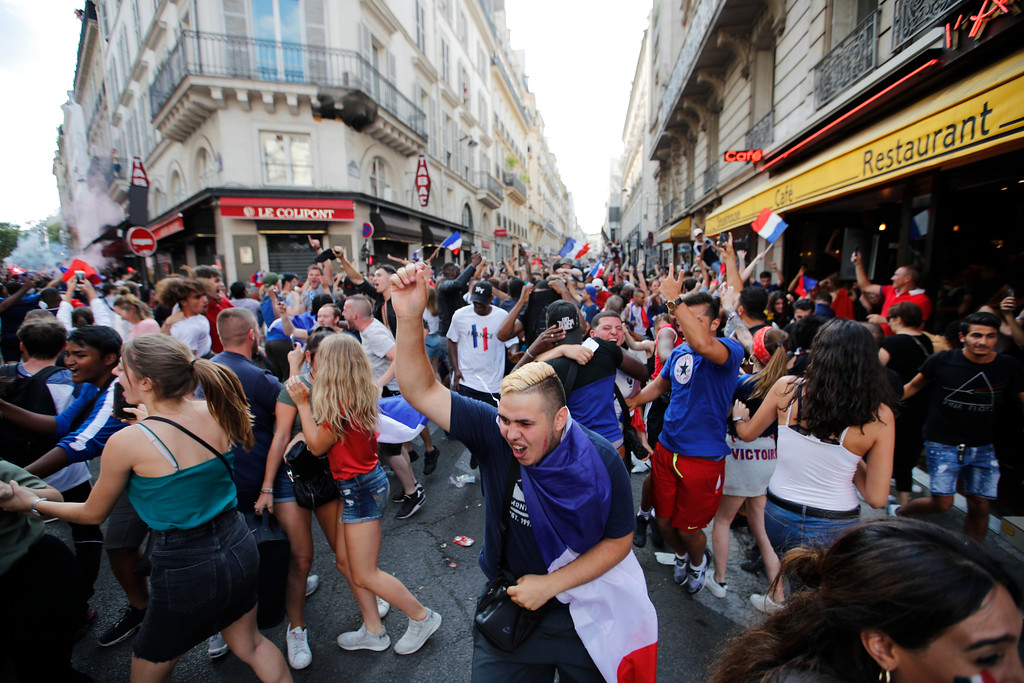 . French soccer team supporters celebrate in a street after France won the soccer World Cup final match between France and Croatia, Sunday, July 15, 2018 in a cafe in Paris. France won its second World Cup title by beating Croatia 4-2 . (AP Photo/Francois Mori)
