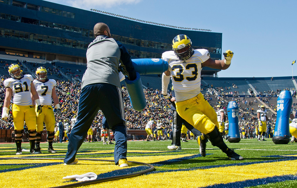 . Michigan defensive end Taco Charlton (33) runs around a blocking drill during the football team\'s annual spring game, Saturday, April 5, 2014, in Ann Arbor, Mich. (AP Photo/Tony Ding)