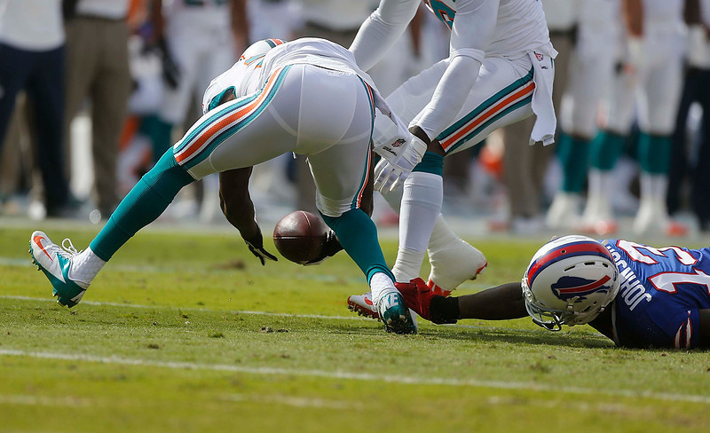 . Miami Dolphins free safety Reshad Jones, left, recovers a fumble by Buffalo Bills wide receiver Steve Johnson (13) during the first half of an NFL football game on Sunday, Dec. 23, 2012, in Miami. (AP Photo/John Bazemore)