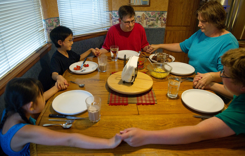 . WESTMINSTER, CO. -  JULY 5:  Summer Love series. The Ericksen family gathers at their Westminster home for their evening meal  on Friday, July 5, 2013.  The family says a prayer at the start of dinner, Eva, 9, Declan, 8 1/2, Christopher, Alyssa and  Brennen, 15.  (Photo By Cyrus McCrimmon/The Denver Post)