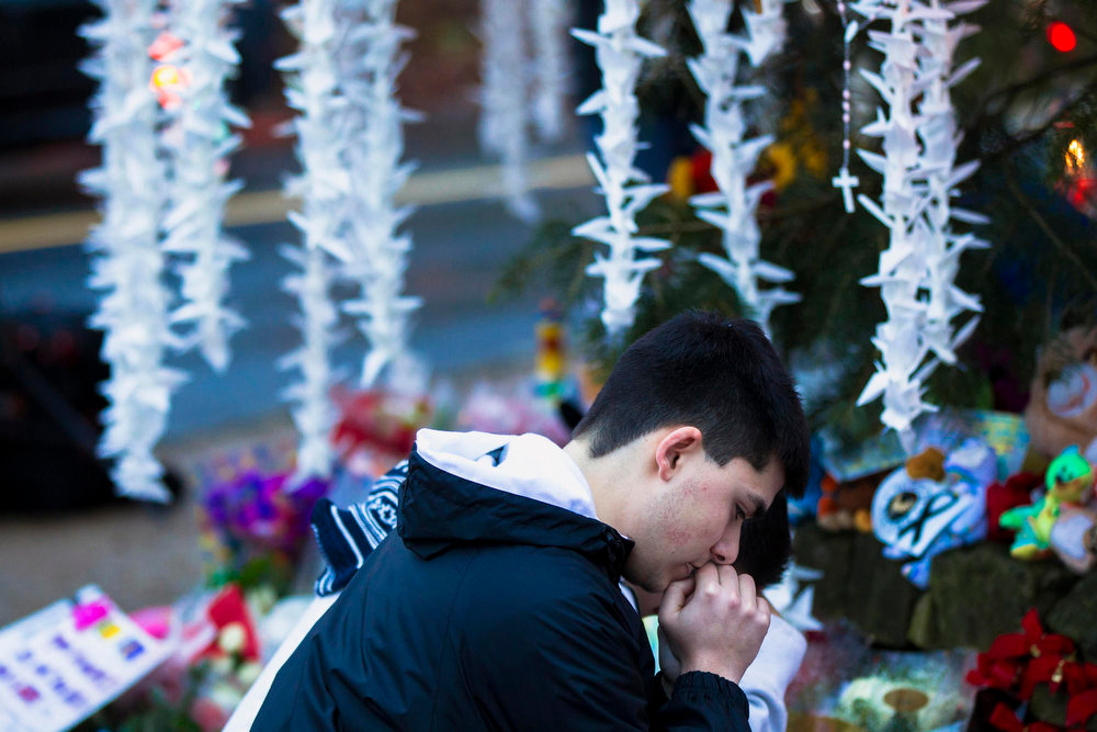 Description of . A man prays while visiting a memorial to the victims of the recent shooting in Sandy Hook Village in Newtown, Connecticut, December 17, 2012. The small Connecticut town shattered by an act President Barack Obama called