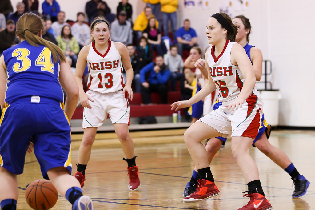 . Sacred Heart\'s Bainy Scully, (15) and Riley Terwilliger, (13) try to stop Carson City-Crystal\'s Mackenzie Geister, (34) from advancing up court at Sacred Heart Thursday, Jan. 23, 2014. Carson City-Crystal won 50-23.  (Sun photo by KEN KADWELL/@KenKadwell).